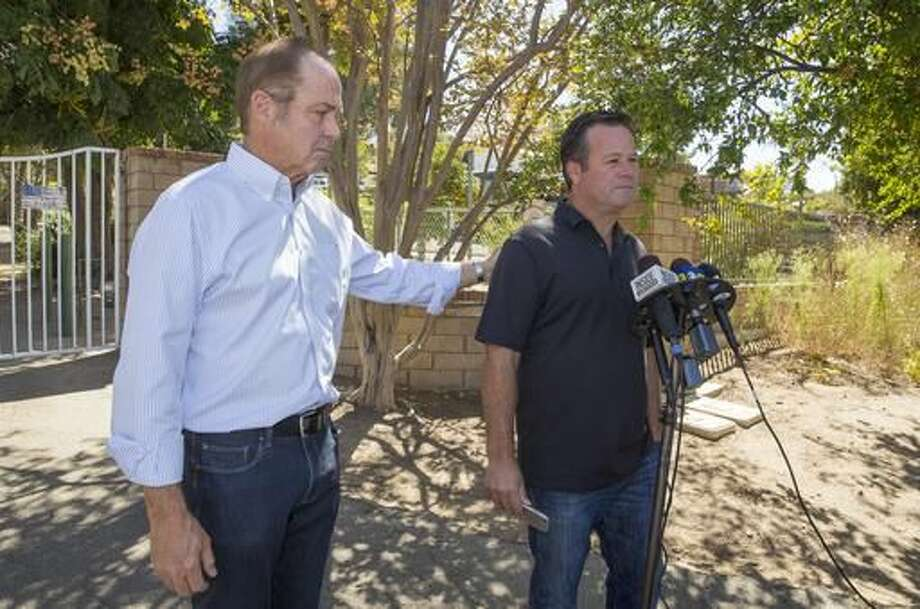 Former NASCAR racer Robby Gordon, right, with family friend Steve Nichols, left, makes a statement to member of the media gathered outside his home in Orange, Calif., on Sept. 15, 2016. Gordon says his family is in shock and grieving the loss of his father and stepmother, who were found dead inside their Southern California home. Gordon spoke briefly to reporters Thursday near the gated house where police discovered the bodies of 68-year-old Robert Gordon and 57-year-old Sharon Gordon. (AP Photo/Damian Dovarganes)