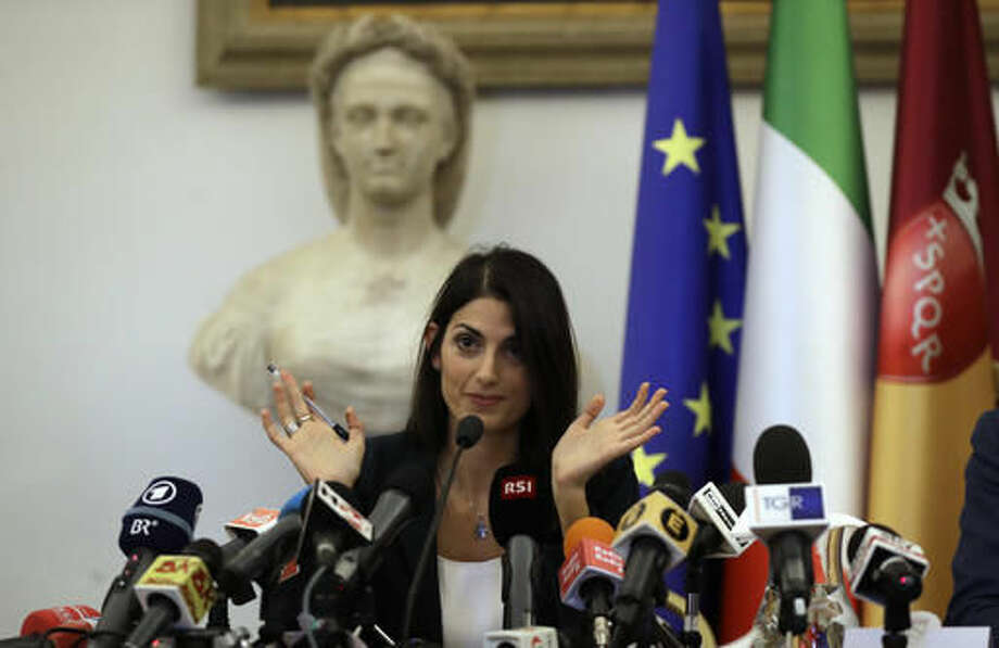 Rome Mayor Virginia Raggi gestures during a press conference after she did not show up at a scheduled meeting with a delegation of the Italian Olympic Committee, in Rome, Wednesday, Sept. 21, 2016. Raggi says it's irresponsible to bid for 2024 Olympic Games, effectively dooming Rome's candidacy. (AP Photo/Alessandra Tarantino)
