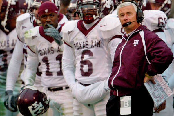 Texas A&M defensive back Byron Jones, left, Bryant Singleton, center, and head coach Dennis Franchione, right, keep an eye on the scoreboard in the closing minutes of their Big 12 game against Oklahoma in Norman, Okla., Saturday, Nov. 8, 2003. Oklahoma won the game 77-0.  (AP Photo/Sue Ogrocki)  HOUCHRON CAPTION (11/09/2003):  Top-rated Oklahoma thrashed Texas A&M 77-0 to avenge last year's upset loss to the Aggies.  HOUCHRON CAPTION (11/09/2003):  Texas A&M coach Dennis Franchione, right, and his players had that shellshocked look at they say on the scoreboard something no Aggies team had suffered in the school's history - a 77-point defeat.