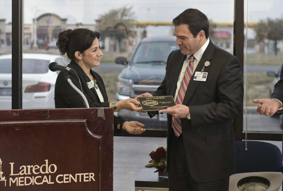 Liz Saldivar presents Laredo Medical Center Chief Executive Officer Enrique Gallegos with a Laredo Chamber of Commerce plaque on Wednesday morning during a ribbon-cutting ceremony for Laredo CareNow.