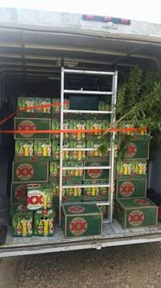 The Austin Police Department and other agencies seized hundreds of 12-packs of beer along with about 20 firearms, drugs and lots of U.S. cash. Photo: Austin Police Department