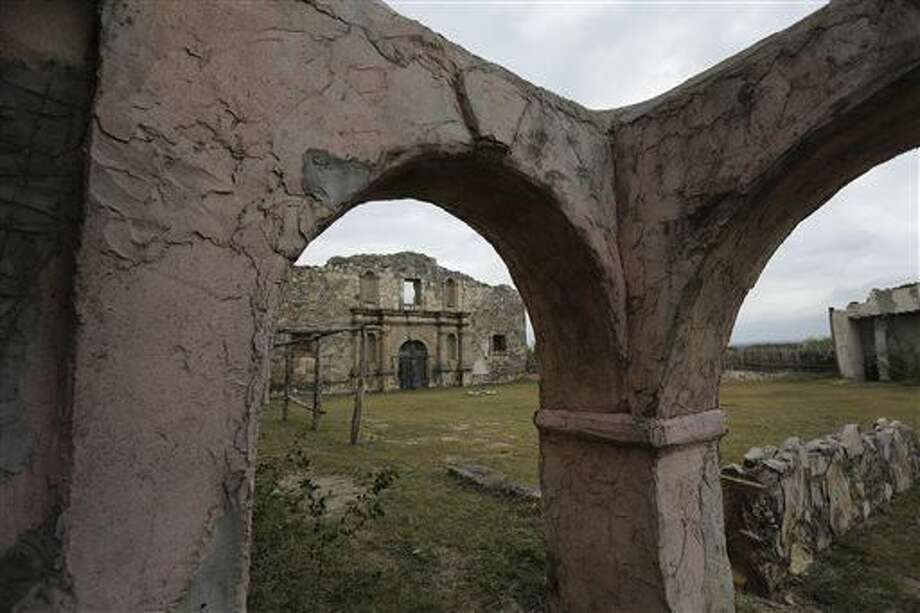 "In this Dec. 4, 2014 photo, a replica of the Alamo built for John Wayne's 1960 movie ""The Alamo,"" is framed by arches at the movie set in Brackettville, Texas. Time and Mother Nature are threatening to dismantle the Alamo. Not the original, but the replica 18th Century Spanish mission and Old West movie set Wayne built for his Oscar-nominated movie and that for decades was a tourist mecca and film production site. (AP Photo/Eric Gay)"