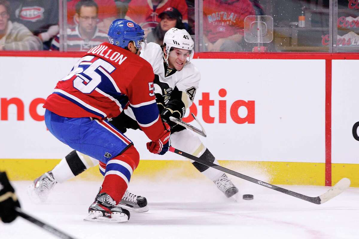 MONTREAL, QC - NOVEMBER 23: Brian Gibbons #49 of the Pittsburgh Penguins passes the puck in front of Francis Bouillon #55 of the Montreal Canadiens during the NHL game at the Bell Centre on November 23, 2013 in Montreal, Quebec, Canada. The Canadiens defeated the Penguins 3-2. (Photo by Richard Wolowicz/Getty Images) ORG XMIT: 181111134 ORG XMIT: MER2016102011450773