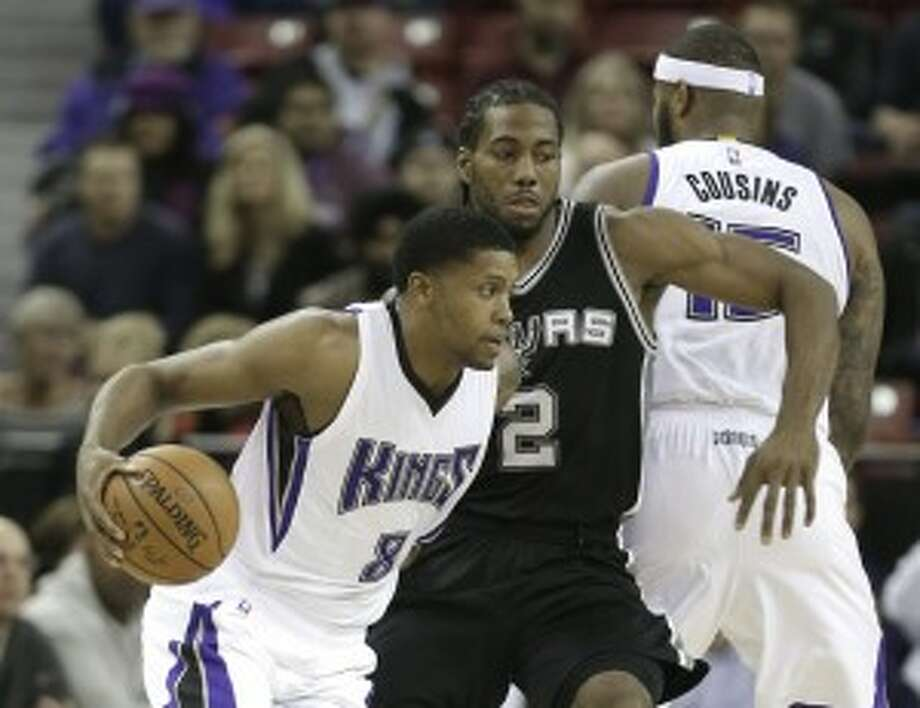 Sacramento Kings forward Rudy Gay, left, drives against San Antonio Spurs forward Kawhi Leonard during the first quarter of an NBA basketball game in Sacramento, Calif., Monday, Nov. 9, 2015.(AP Photo/Rich Pedroncelli)