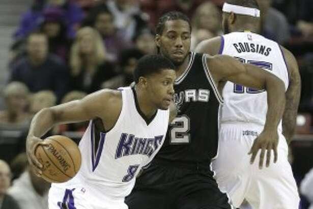 Sacramento Kings forward Rudy Gay, left, drives against San Antonio Spurs forward Kawhi Leonard during the first quarter of an NBA basketball game in Sacramento, Calif., Monday, Nov. 9, 2015.(AP Photo/Rich Pedroncelli)