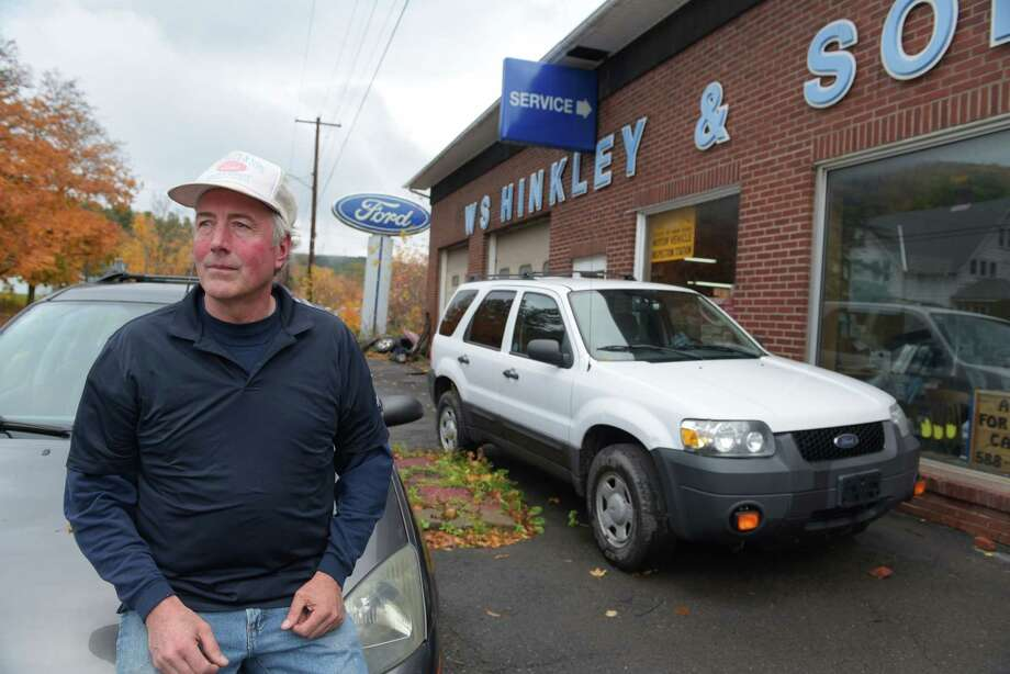 and sons ford dealership poses for a photo outside his dealership. Cars Review. Best American Auto & Cars Review