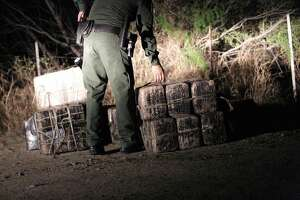 After chasing away the smugglers using rafts to bring drugs across the river, Border Patrol and Texas DPS agents inspect several large packages of marijuana abandoned near the Rio Grande shoreline near Roma, Texas, on March 8.