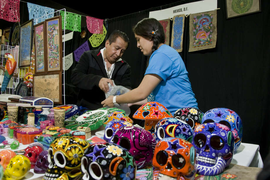 In this file photo, Alberto Martinez and Alejandra Eligido wrap up one of the curios purchased by a customer at the Laredo Energy Arena during the Sister Cities Festival.