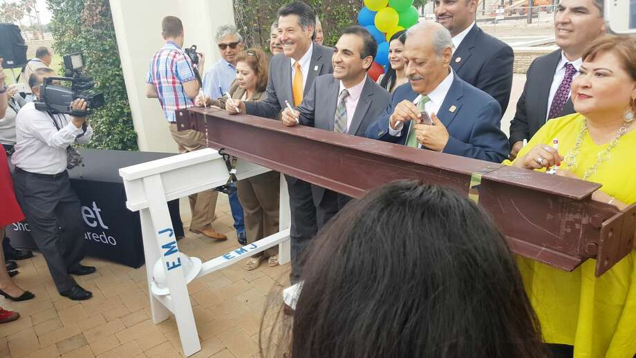 """City of Laredo officials, including (front row) Deputy City Manager Cynthia Collazo, Mayor Pete Saenz, District VIII Council Member Roberto Balli and Mayor Pro Tempore Juan Narvaez were joined by the Laredo community and Webb County officials, including Precinct 2 Commissioner Rosaura """"Wawi"""" Tijerina, and (back row) Claudia Balli, Webb County Judge Tano Tijerina and Precinct 4 Commissioner Jaime Canales, while Horizon CEO Gary Skoien looks, as they sign a steel beam that will soon be a part of the permanent structure of The Outlet Shoppes of Laredo, the downtown outlet mall that will be completed in spring 2017."""