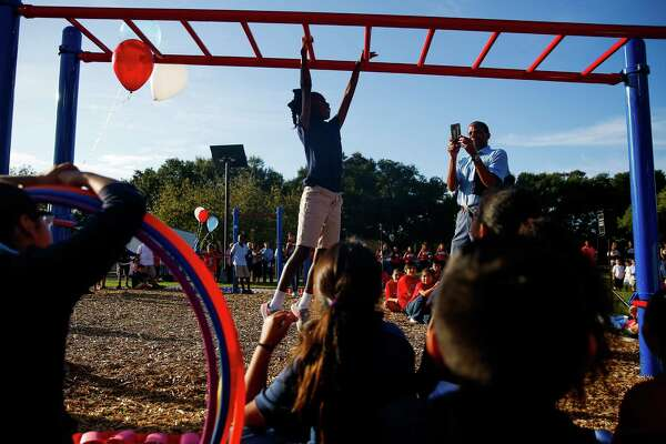 A Bowie Elementary School student demonstrates exercises on playground equipment donated to the school by Memorial Hermann as they launch a new school fitness program to help kids overcome problems like obesity Wednesday, Oct. 19, 2016 in Rosenberg. ( Michael Ciaglo / Houston Chronicle )