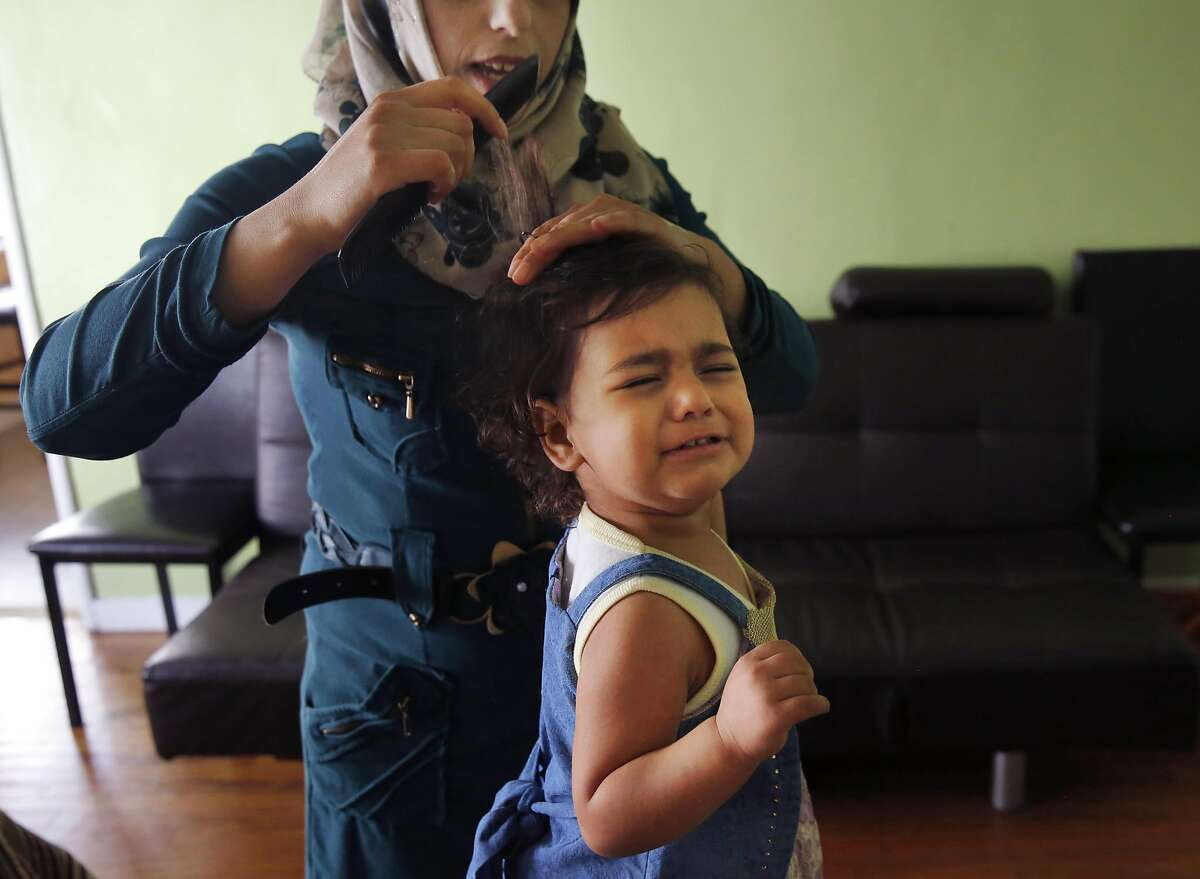 Hadeel Jabr, 25, brushes the hair of her protesting daughter Nisreen Hussien, 1, in their family apartment Oct. 20, 2016 in Oakland, Calif. The Syrian family has recently been resettled in Oakland after spending a few years in Jordan after fleeing the Syrian civil war.