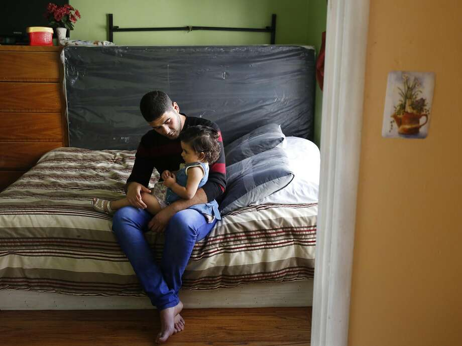 Mohanad Hussien, 23, sits on the bed with his daughter Nisreen Hussien, 1, in the family apartment Oct. 20, 2016 in Oakland, Calif. The Syrian family has recently been resettled in Oakland after spending a few years in Jordan after fleeing the Syrian civil war. Photo: Leah Millis, The Chronicle