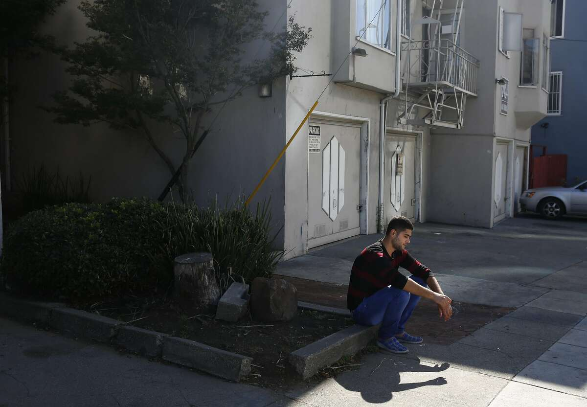 Mohanad Hussien, 23, takes a smoke break outside of his apartment Oct. 20, 2016 in Oakland, Calif. The Syrian family has recently been resettled in Oakland after spending a few years in Jordan after fleeing the Syrian civil war.