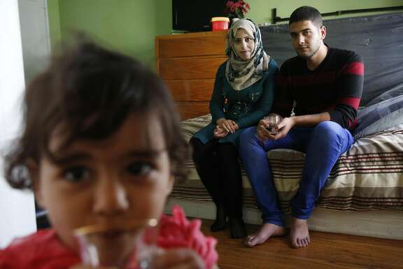 Family members, from left daughter Nisreen Hussien, 1, Hadeel Jabr, 25, and her husband Mohanad Hussien, 23, sit on their bed, in their apartment for a portrait Oct. 20, 2016 in Oakland, Calif. The Syrian family has recently been resettled in Oakland after spending a few years in Jordan after fleeing the Syrian civil war.