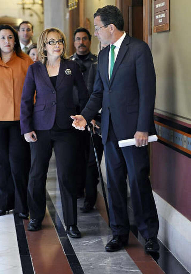 FILE - In this March 17, 2015 file photo, former Arizona U.S. Rep. Gabby Giffords, left, walks to a meeting at the state Capitol in Hartford, Conn., with Connecticut Gov. Dannel P. Malloy, right. Giffords was visiting to push for a gun control measure that would prevent subjects of a court-ordered temporary restraining order from being able to possess firearms or ammunition during the days leading up to their hearing. That legislation is one of the new state laws that takes affect on Oct. 1, 2016. (AP Photo/Jessica Hill, File)