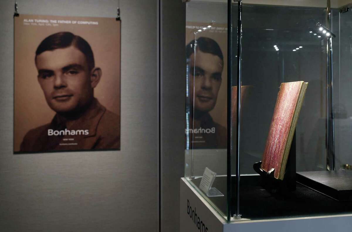 FILE - In this Thursday, March 19, 2015 file photo, a notebook of British mathematician and pioneer in computer science Alan Turing, the World War II code-breaking genius, is displayed in front of his portrait during an auction preview in Hong Kong. Britain's government will posthumously pardon thousands of gay and bisexual men convicted under long-repealed anti-gay laws. The calls for a more sweeping action came after World War II codebreaker Alan Turing was awarded a posthumous royal pardon in 2013 after a conviction of indecency in 1952. The gay computer science pioneer was stripped of his security clearance and later committed suicide. (AP Photo/Kin Cheung, File)