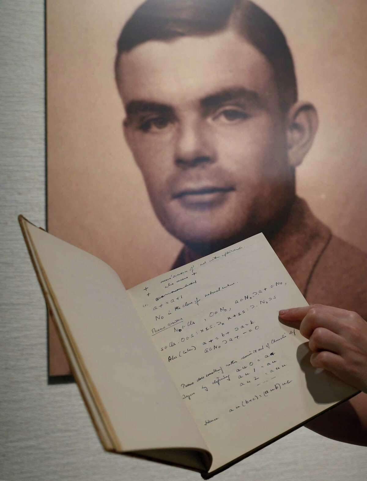 FILE - In this March 19, 2015 file photo, a page from the notebook of Alan Turing, the World War II code-breaking genius, is displayed in front of his portrait at an auction preview in Hong Kong. Turing, who was convicted of indecency in 1952 for being gay and later killed himself, was awarded a posthumous royal pardon in 2013. Britain's government announced Thursday, Oct. 20, 2016, that it will posthumously pardon thousands of gay and bisexual men convicted under the long-repealed anti-gay laws. (AP Photo/Kin Cheung, File)