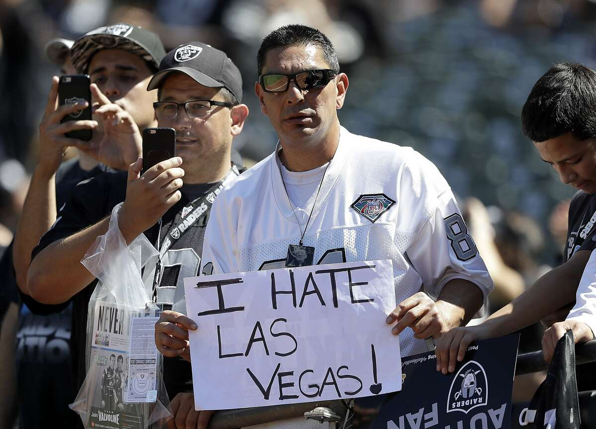 An Oakland Raiders fan holds up a sign about the team possibly relocating to Las Vegas before an NFL football game between the Oakland Raiders and the Atlanta Falcons in Oakland, Calif., Sunday, Sept. 18, 2016. (AP Photo/Marcio Jose Sanchez)