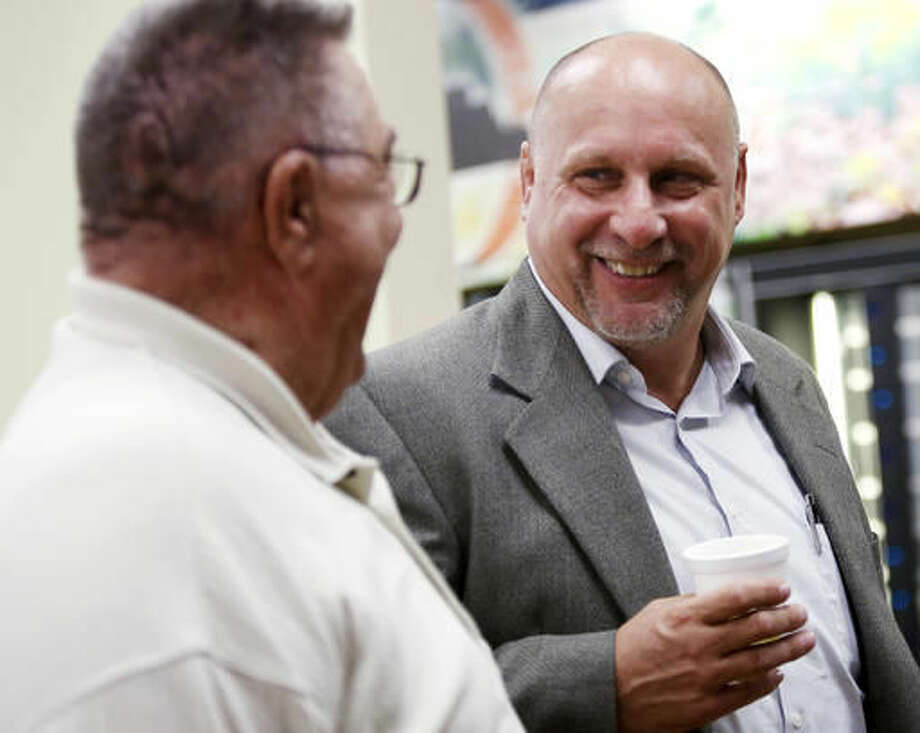 Brad Nelson, right, talks with his father, David Nelson, left, and others during his retirement party Thursday, Sept. 22, 2016, at the Olmsted County Government Center in Rochester, Minn. Brad retired after 29 years with the Sheriff's Office. (Andrew Link /The Rochester Post-Bulletin via AP)