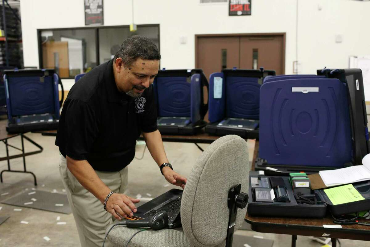 Bexar County Elections Office supervisor of operations Joe Camacho shown in October 2016 loading election information into voting machines for the general election that year. Camacho and his team have been busier than usual during the current record-breaking election season.