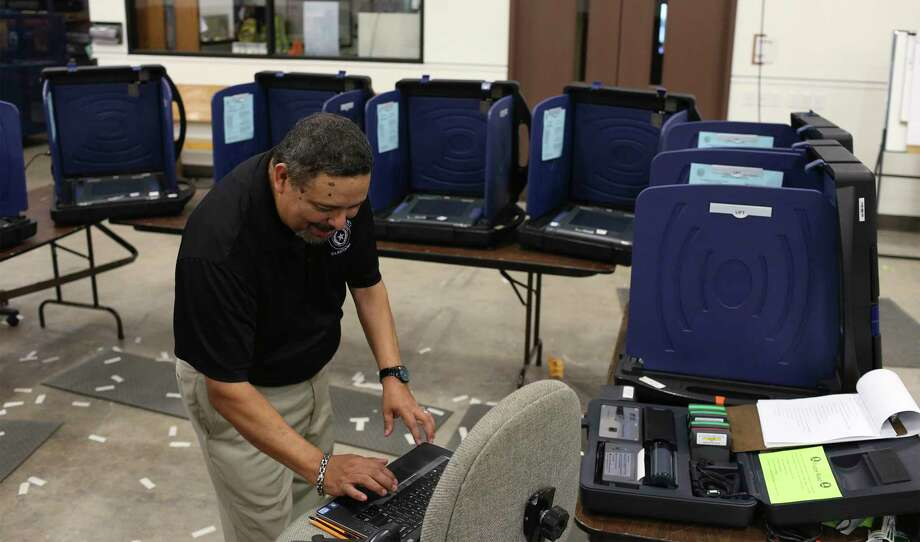 Bexar County Elections Department operations coordinator Joe Camacho loads election information into voting machines for the general election in Ocotober 2016. Photo: JERRY LARA /San Antonio Express-News / © 2016 San Antonio Express-News