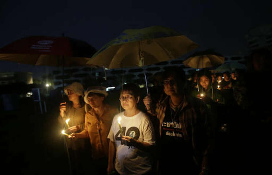 Thai activists hold a candlelight vigil at Thammasat University in Bangkok, Thailand, Thursday, Oct. 6, 2016. Buddhist monks, mourners, activists and others gathered Thursday to mark the 40th anniversary of one of the darkest days in Thailand's history, when police killed scores of university students at a peaceful protest, and ghoulish vigilantes defiled the dead. (AP Photo/Sakchai Lalit)