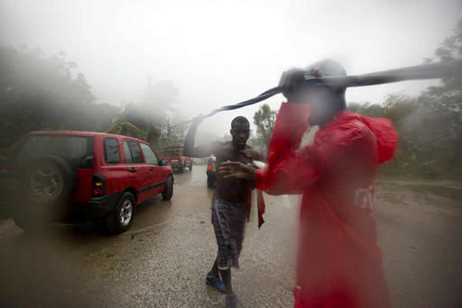 Two men remove a downed power line to allow vehicles passage, in Petit Goave, Haiti, Tuesday, Oct. 4, 2016. Matthew slammed into Haiti's southwestern tip with howling, 145 mph winds Tuesday, tearing off roofs in the poor and largely rural area, uprooting trees and leaving rivers bloated and choked with debris. ( AP Photo/Dieu Nalio Chery)