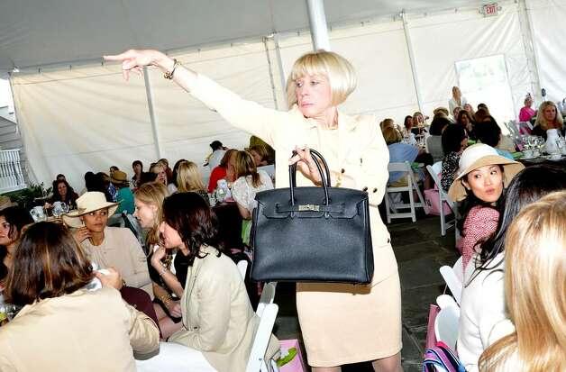 Mary Ann Henry Acknowledges A Bidder As She Models Hermes Black Togo Birkin Bag With