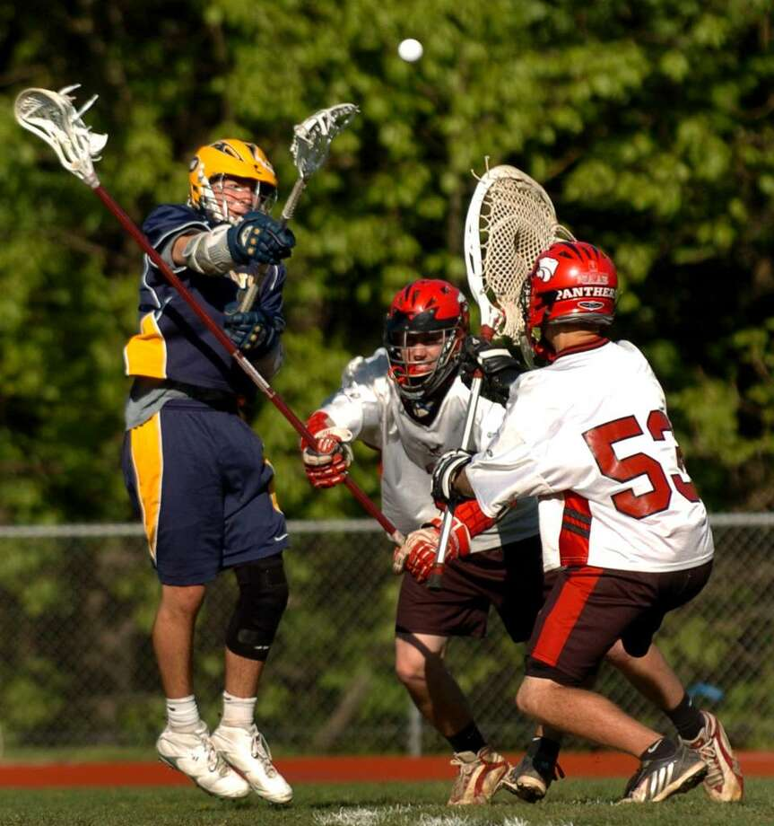 Weston's Jack Scheufele, left, send the ball past Masuk goalie Charles Porzelt for a goal, during lacrosse action in Monroe, Conn. on Friday May 07, 2010. Trying to block in the middle is Masuk's #3 Tim Treschitta. Photo: Christian Abraham / Connecticut Post