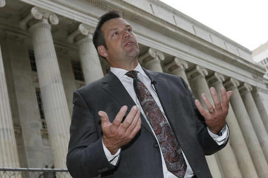 """FILE - In this Aug. 23, 2016 file photo, Kansas Secretary of State Kris Kobach responds to questions outside the 10th U.S. Circuit Court of Appeals in Denver. A federal appeals court says """"no constitutional doubt arises"""" that federal law prohibits Kansas from requiring citizenship documents from people who register to vote at motor vehicle offices. The ruling handed down late Friday evening, Sept. 30, 2016, upholds U.S. District Judge Julie Robinson's temporary order forcing Kansas to register more than 20,000 voters. The decision is the latest setback for Kobach. (AP Photo/David Zalubowski, File)"""