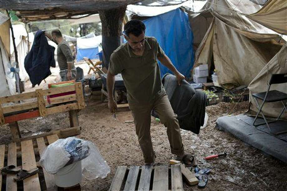 """In this Thursday, Sept. 22, 2016 photo, 43-year-old Yousef Hanash from Ibdil in Syria walks in mud near his tent after rainfall at the Ritsona camp for refugees and other migrants north of Athens. Hanash said he, his wife and three children _ a fourth was born to them in Greece _ came to Europe as a last resort after fighting destroyed his cheese factory. """"But there is nothing for us to do here, life here is miserable,"""" he said. """"All we can do is deal with the weather, the heat, the cold and the rain."""" (AP Photo/Petros Giannakouris)"""