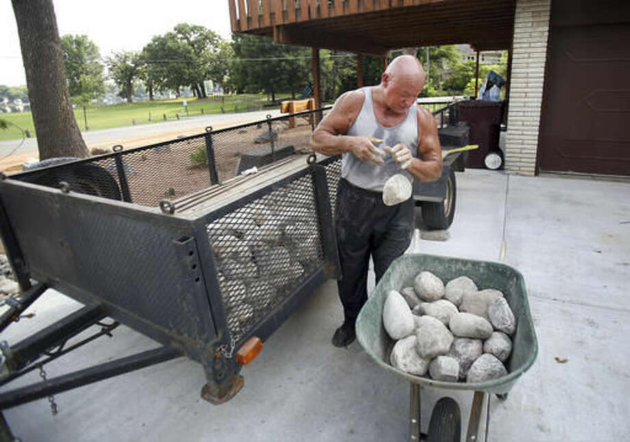 In this Sept. 7, 2016 photo, Alex Rothacker sorts through rocks as he transforms his yard into a desert, in Wildwood, Ill. He's a huge fan of the desert landscape. So much so he turned his green yard into a desert scape of rocks, gravel and cactuses. Rothacker admires the decor of the desert and describes it as clean and fresh. (Steve Lundy/Daily Herald, via AP)