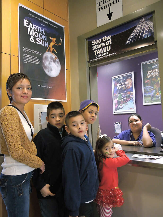 Maria Soliz and her children Angel, Daniel, Vianey and Christian get their ticket to see an afternoon show at the TAMIU Planetarium Monday. Planetarium employee Claudia Herrea, and others were on hand for an open house.