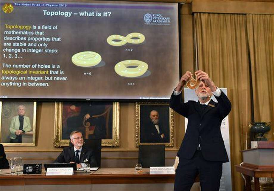 Professor Thors Hans Hansson gives a demonstration, after revealing the winners of the Nobel Prize in physics, at the Royal Swedish Academy of Sciences, in Stockholm, Sweden, Tuesday, Oct. 4, 2016. David Thouless, Duncan Haldane and Michael Kosterlitz have won the Nobel physics prize. Nobel jury praises physics winners for 'discoveries of topological phase transitions and topological phases of matter'. (Anders Wiklund /TT via AP)