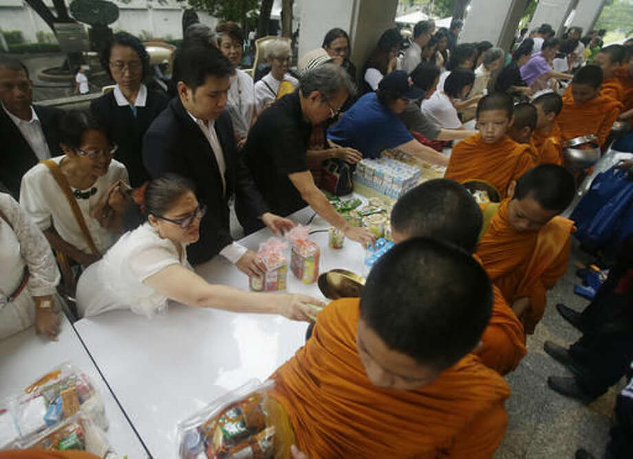Thai people offer food to novice monks at Thammasat University in Bangkok, Thailand, Thursday, Oct. 6, 2016. Buddhist monks, mourners, activists and others gathered Thursday to mark the 40th anniversary of one of the darkest days in Thailand's history, when police killed scores of university students at a peaceful protest, and ghoulish vigilantes defiled the dead. (AP Photo/Sakchai Lalit)