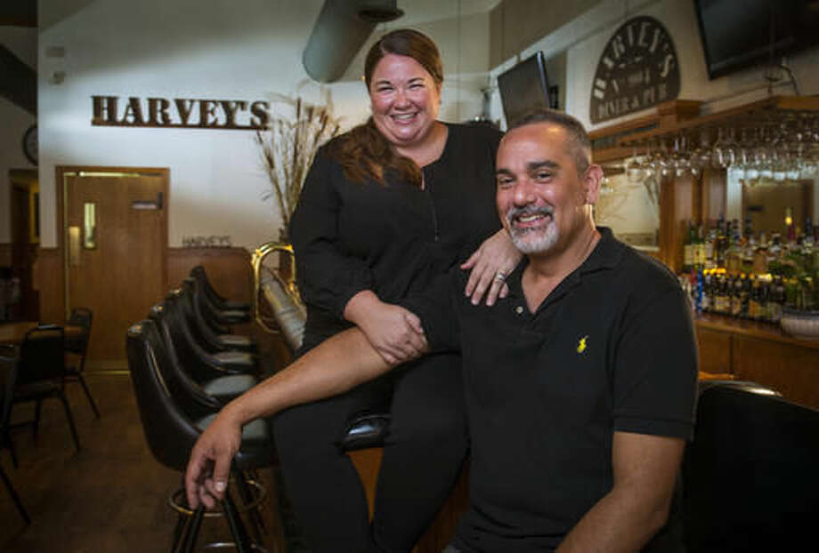 In this Aug. 15, 2016 photo, Katie Harvey-Martinez and husband Rick pose in their recently opened restaurant Harvey's Diner & Pub (formally Dexfield Diner) in Redfield, Iowa. (Rodney White /The Des Moines Register via AP )