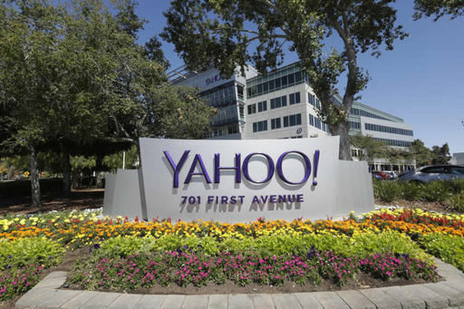 "In this Tuesday, July 19, 2016, photo, flowers bloom in front of a Yahoo sign at the company's headquarters in Sunnyvale, Calif. Yahoo responded again on Wednesday, Oct. 5, 2016, to a report that it scanned incoming email to hundreds of millions of accounts for the U.S government. In a carefully worded statement that stops short of a denial, the company said a Tuesday Reuters report is ""misleading,"" saying that ""the mail scanning described in the article does not exist on our systems."" (AP Photo/Marcio Jose Sanchez)"