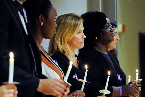 At center, Brooke Bremer, of Greenwich, holds a candle in memory of victims of domestic abuse during the YWCA Greenwich's Domestic Abuse Services annual candlelight vigil on Thursday.