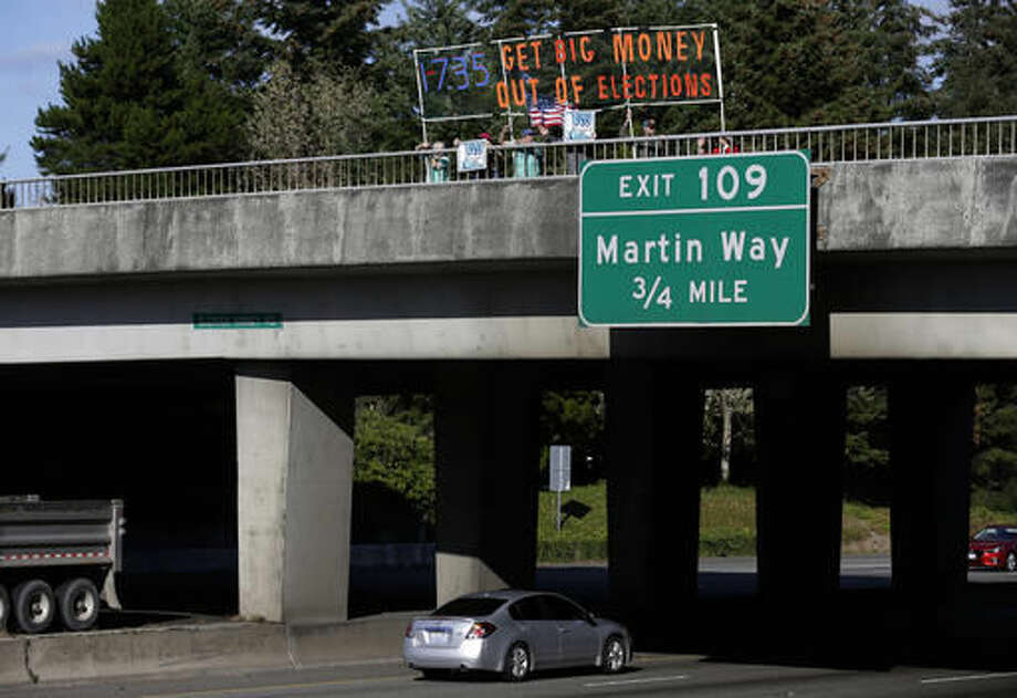 In this photo taken Sept. 22, 2016, supporters of Initiative 735 hold a banner above the I-5 freeway during the evening commute in Lacey, Wash. Proponents of the statewide ballot initiative want to get big money out of politics by backing a federal constitutional amendment that says free speech in the form of political contributions belongs to people, not corporations. Opponents of the measure say the government shouldn't limit the First Amendment. (AP Photo/Ted S. Warren)