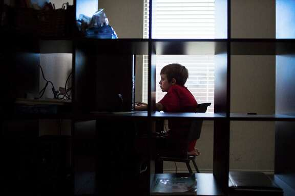 A silhouette of Steven Smith, 11, is seen through a bookshelf in his bedroom in Leander while he uses his home desktop computer. Smith was born with autism and without functional hands. Smith depends mostly on the use of computers to do his school work. While Smith and his family lived in Illinois he was provided a laptop by the school for his homework but when he moved back to Texas, Doss Elementary told the family they would have to wait eight weeks for an evaluation for this to be even considered even though his his doctors stated that he needs a laptop based on his orthopedic impairment.  Wednesday, Oct. 5, 2016, in Leander.