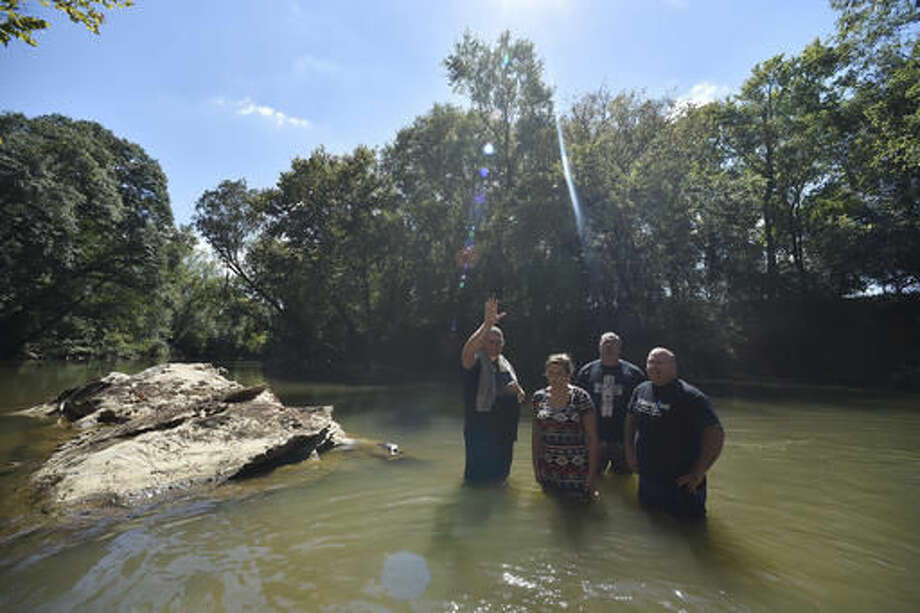 Resaca Church Of God Pastor Mitchell Gaston, left, prays with others as they baptize Ellie Langford, 12, in the Coosawattee river, Sunday, Sept. 25, 2016, near Calhoun, Ga. Many denominations don't fully immerse baptismal candidates, preferring to sprinkle them with water. And in churches that do immersion baptism, water tanks built inside the church's sanctuary have largely replaced excursions to dunk members in a river or pond. (AP Photo/Mike Stewart)