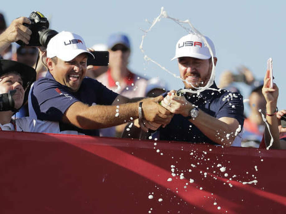 United States' Patrick Reed and United States' Jimmy Walker sprays fans with Champagne after the United States team won the Ryder Cup golf tournament Sunday, Oct. 2, 2016, at Hazeltine National Golf Club in Chaska, Minn. (AP Photo/Charlie Riedel)