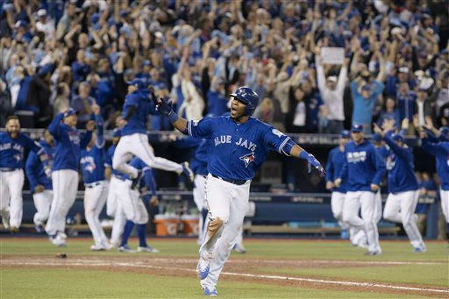 Toronto Blue Jays' Edwin Encarnacion celebrates while he rounds the bases after hitting a walk-off three-run home run during the 11th inning of an American League wild-card baseball game in Toronto, Tuesday, Oct. 4, 2016. (Mark Blinch/The Canadian Press via AP)