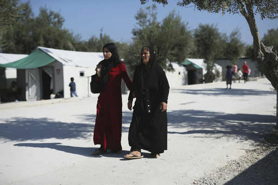 Two Syrian women walk at the Kara Tepe camp for refugees and other migrants on Lesbos island, Greece, on Thursday, Oct. 6, 2016. More than a million migrants and refugees crossed through Greece and on to other EU countries since the start of 2016, while over 60,000 have been stranded in the country since the EU-Turkey deal took effect and the Balkan transit route north was closed. (AP Photo/Petros Giannakouris)