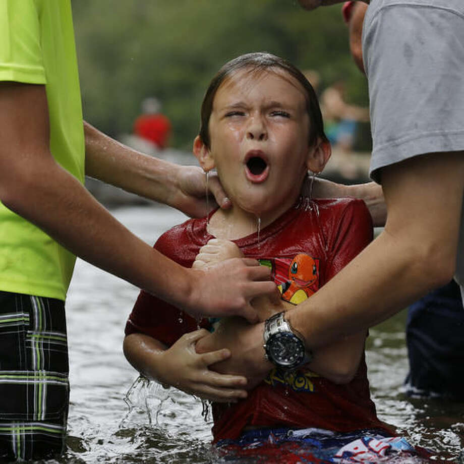 Nicholas Lewis reacts after he was baptized in the Chattahoochee River, Sunday, Sept. 18, 2016, near Demorest, Ga. Many denominations don't fully immerse baptismal candidates, preferring to sprinkle them with water. And in churches that do immersion baptism, water tanks built inside the church's sanctuary have largely replaced excursions to dunk members in a river or pond. (AP Photo/Mike Stewart)