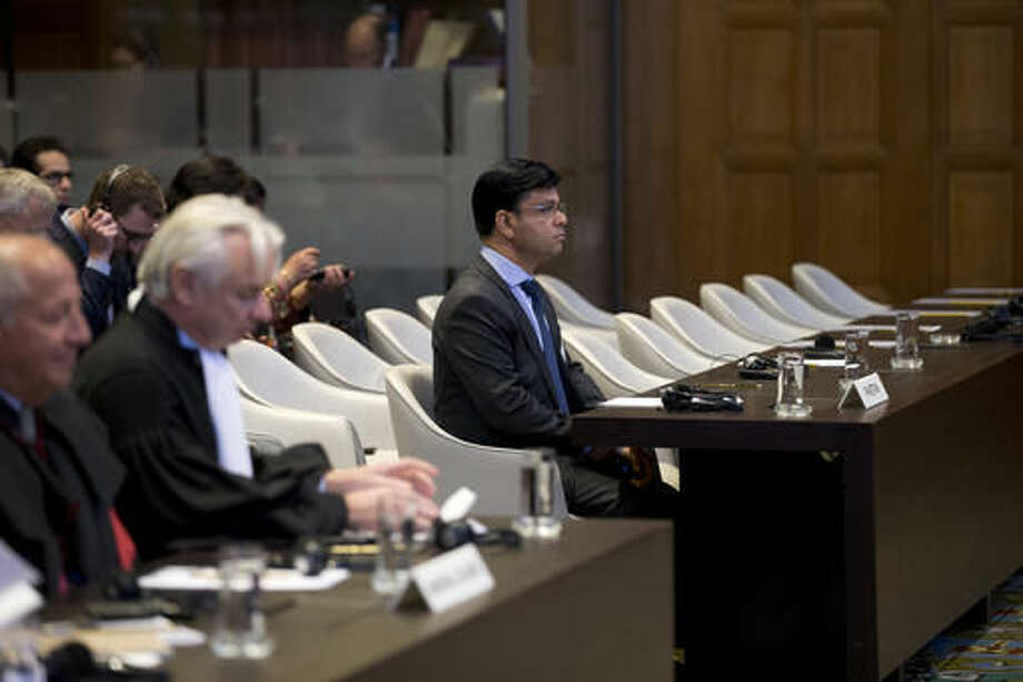 Phon van den Biesen, lawyer for the Marshall Islands, second left, and Pakistan's representative Syed Faraz Hussain Zaidi, counsellor of the Embassy of Pakistan, center, wait for the start of the World Court session in The Hague, Netherlands, Wednesday, Oct. 5, 2016. The Marshall Island are taking India, Pakistan and the U.K. to court to urge those powers to resume negotiations to eradicate the world's nuclear stockpile, the court handed down three separate rulings. (AP Photo/Peter Dejong)