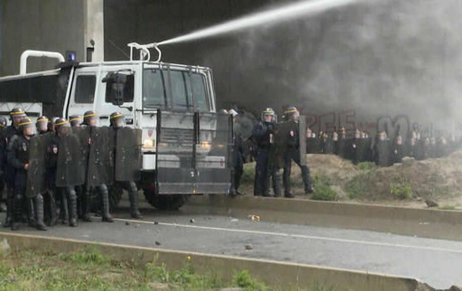 In this grab taken from video, french police spray protester using a water cannon, during a demonstration in Calais, France, Saturday, Oct. 1, 2016. French police have fired tear gas and water cannons on protesters defending migrants in the northern city of Calais as the government prepares to shut down the city's notorious migrant camp. (AP)