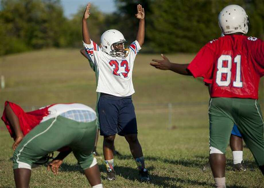 In this Monday, Oct. 3, 2016 photo, Central Hayneville High School football player Swanique Gordon interacts with teammates as she practices at the school near Hayneville, Ala. Gordon, a girl, is a starting linebacker with the team. (Mickey Welsh/The Montgomery Advertiser via AP)