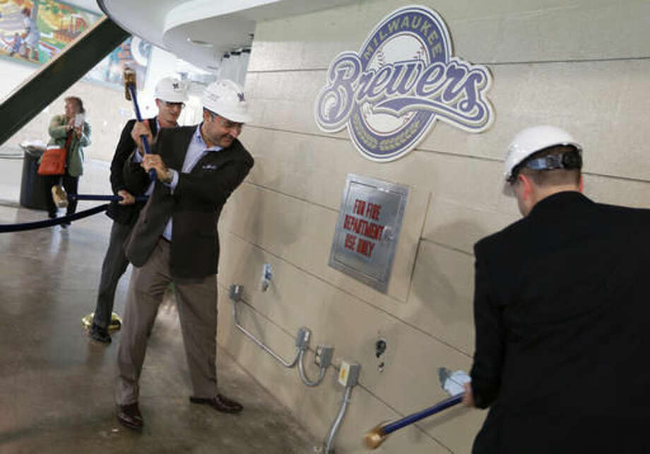Brewers Chief Operating Officer Rick Schlesinger, from left, John Sergi, the co-owner Howard and Sergi, a hospitality design consultant, and Ken Gaber, general manager with food services Delaware North, participate in a ceremonial wall demolition on an old concession stand on the third base side in what will be the new third base ward at Miller Park baseball stadium in Milwaukee, Wis., Wednesday, Oct. 5, 2016. As the Milwaukee Brewers reshape their on-the-field roster, the home ballpark will undergo the single largest improvement since it opened in 2001, team executives said Wednesday. (Mike De Sisti/Milwaukee Journal-Sentinel via AP)