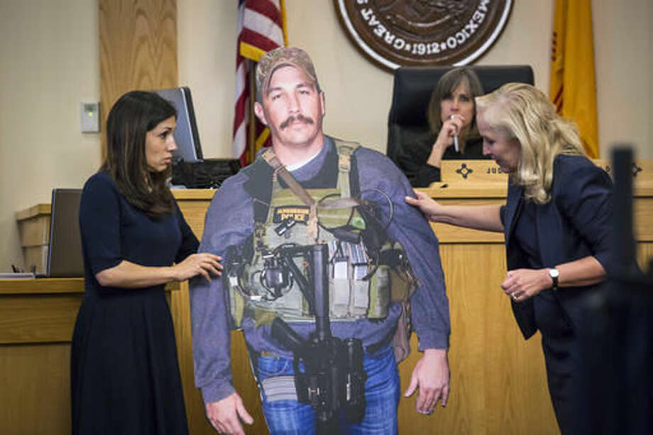 Prosecutors Elicia Montoya, left, and Randi McGinn present a life-size cut out of former Albuquerque Police Detective Keith Sandy, Wednesday, Oct. 5, 2016 in Albuquerque, N.M.. Attorneys in the jury trial of two former police officers charged in the killing of a homeless camper have attempted to reconstruct the scene of the standoff that ended with the officers fatally shooting the man in the arms and back. (AP Photo/Juan Labreche)